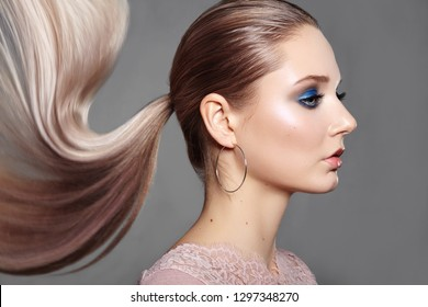 Beautiful Girl with Ponytail Hairstyle. Blond Shiny Straight Hair, Fashion Makeup on Model Face. Woman with Healthy Skin and Party Glitter Make-up