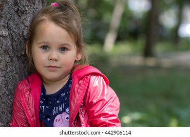 Beautiful girl with a ponytail in red jacket near the tree