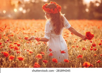 beautiful girl in a poppy field at sunset