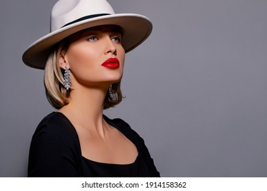 Beautiful girl portrait. Fashionable and stylish woman in trendy jewelry big earrings with stones. elegant model in white hat, red lips makeup. Fashion look, beauty and style. Gray background
