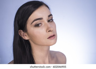 Beautiful girl. Portrait of a girl in make-up beauty on a blue background. Woman with make-up beauty. Brunette on a blue background. Beautiful hair. Portrait of a girl with beautiful hair