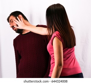 Beautiful girl portrait slapping her boyfriend in the face