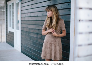 beautiful girl posing on a background of a wooden wall