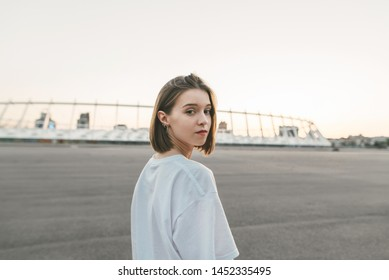 Beautiful girl posing on the evening urban background, looking into the camera, wearing a white T-shirt. Street style portrait.