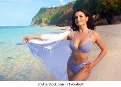 Beautiful girl posing on the sandy beach. On a Sunny day
