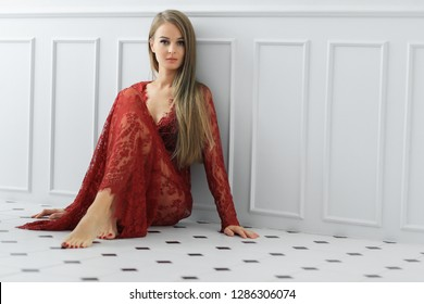 Beautiful girl is posing in a red dress