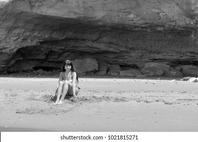 beautiful girl posing sitting on the sand, black and white version