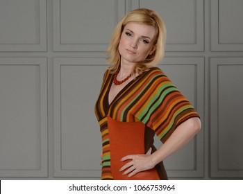 Beautiful girl posing in studio. She is dressed in a striped knitted blouse and white jeans. Clothing in the style of the 1970s. Hands at the waist. Unusual background.