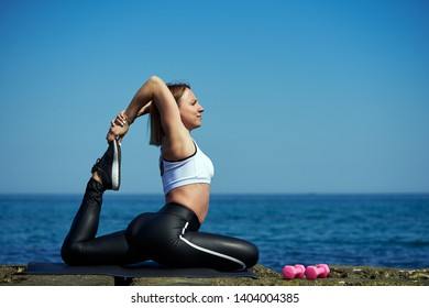 Beautiful girl practices yoga by the sea on a sunny day. The woman does stretching exercises.