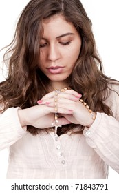 a beautiful girl praying with a rosary on her hands