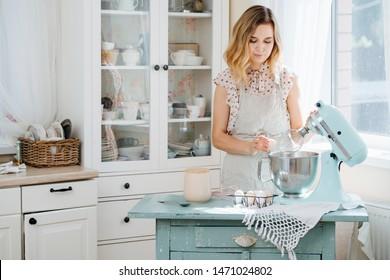schönes Mädchen, das Teig in einem Lebensmittelprozessor zubereitet, während es in einer hellen Küche steht