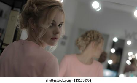 Beautiful girl with professional makeup look at camera reflected at mirror