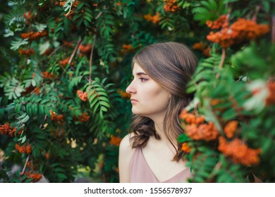 Beautiful girl in profile among the branches of mountain ash