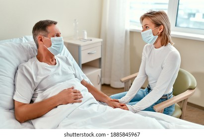 A beautiful girl in a protective medical mask came to visit her dad or grandfather, who is lying in a modern hospital ward during the coronavirus or covid-19 epidemic.