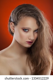 Beautiful girl with pure skin. day make-up on the orange background