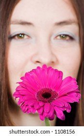 beautiful girl with a beautiful purple daisy with focus on the flower