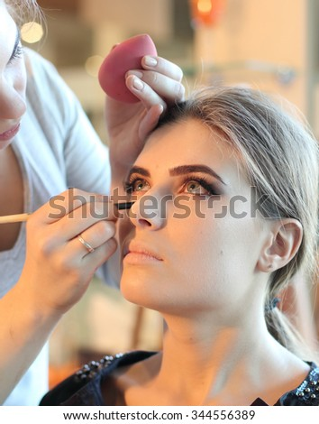 Beautiful girl put the makeup on the face in the beauty salon