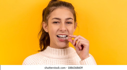 A beautiful girl puts a dental retainer on her teeth, she stands on a yellow background. Orthodontist. Dental tray. Retainer. Place for an inscription.