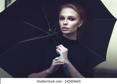 Beautiful girl in the rain with umbrella