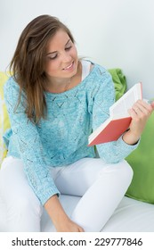beautiful girl read a book at her couch