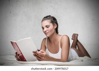 beautiful girl reading a book in the bed
