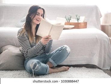 A beautiful girl is reading a book in the living room by the couch