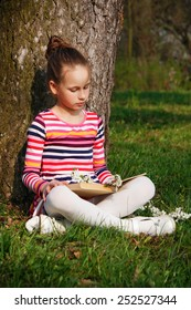 A beautiful girl reading book, sitting near the tree