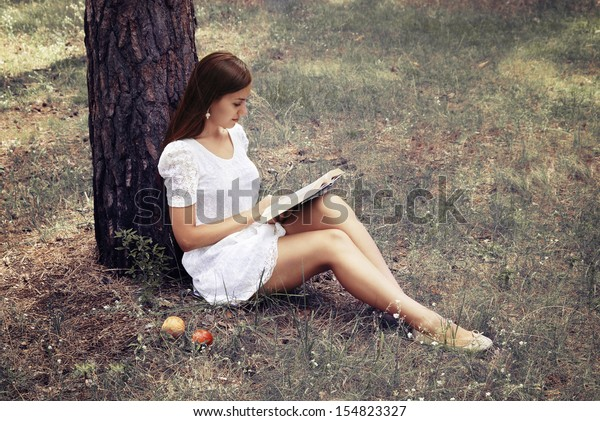 Beautiful girl is reading interesting book while sitting on the grass