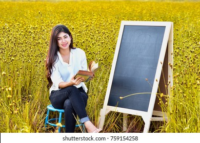Beautiful girl reading old books. The blackboard is next to it.