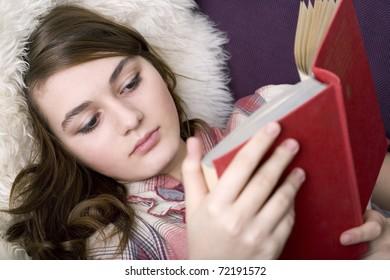 Beautiful girl reads book, closeup portrait