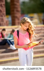 beautiful girl reads textbook on the background of school