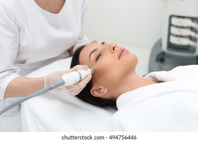 Beautiful girl is receiving anti-aging rejuvenation procedure at spa salon. She is lying with pleasure. Beautician is lifting laser near her cheek