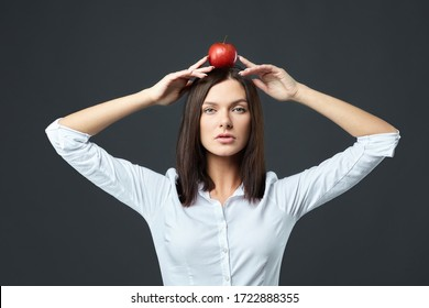 Beautiful girl with a red Apple on a gray background