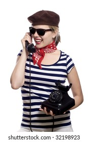 beautiful girl with red bandana, beret and striped shirt in a classic 60s french look is holding an old rotary phone
