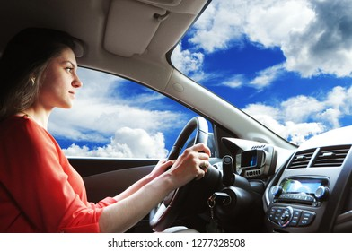 Beautiful girl in red close driving the car on the road
