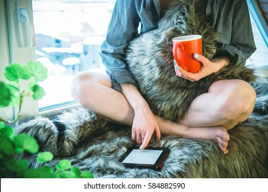 Beautiful girl with red cup is reading a book