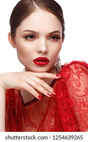 Beautiful girl in red dress with classic make-up and red manicure. Beauty face. Photo taken in the studio.