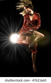 Beautiful girl in red dress dances on black studio background