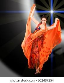 Beautiful girl, beautiful red dress, developed in the wind, beautiful light. frozen dynamics. Woman in red blowing flying red dress dissolving in splash