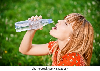 Beautiful girl in red dress drinks water from bottle, against green grass.