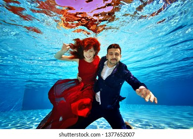 e3d84d2941f69 A beautiful girl in a red dress and a guy in a suit are swimming underwater