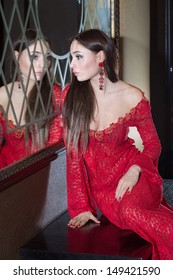 Beautiful girl in the red dress looks in the mirror