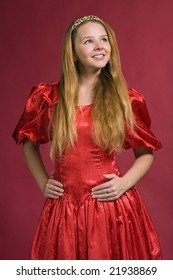 beautiful girl in red dress looks upstairs on red background