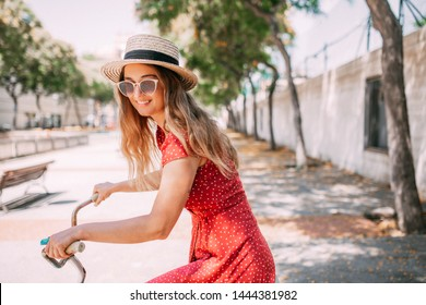 Beautiful girl in red dress making tourism in the sunny sity, walking on the beach having coffe and riding vintage bicycle
