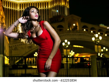 Beautiful girl in a red dress on a background of a night city