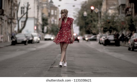 Beautiful girl in red dress posing for camera at urban road with cars