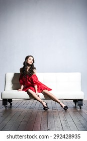 Beautiful girl in a red dress posing on a sofa