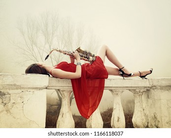 Beautiful girl in red dress with sax lying on the balustrade in the park