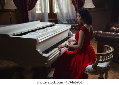 Beautiful girl in red dress sits playing the piano