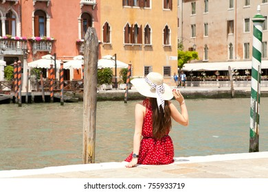 Beautiful girl in red dress standing, in background is The Grand Canal from Venice Italy